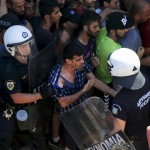 A migrant argues with a riot police officer during a registration procedure at the national stadium of the Greek island of Kos